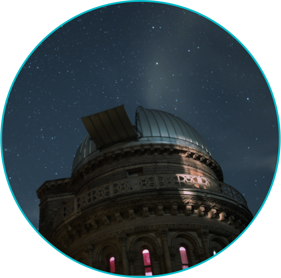 An observatory at night, silhouetted against the starry night sky, consisting of a cylindrical stone structure capped with a metal dome. A hatch on the dome is open, giving a telescope inside a view of the sky.