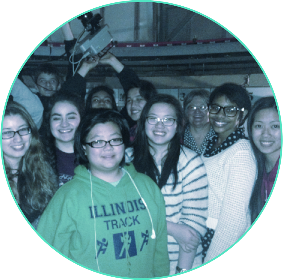 A group of high-school-age students assembled for a group picture inside the dome of an observatory.