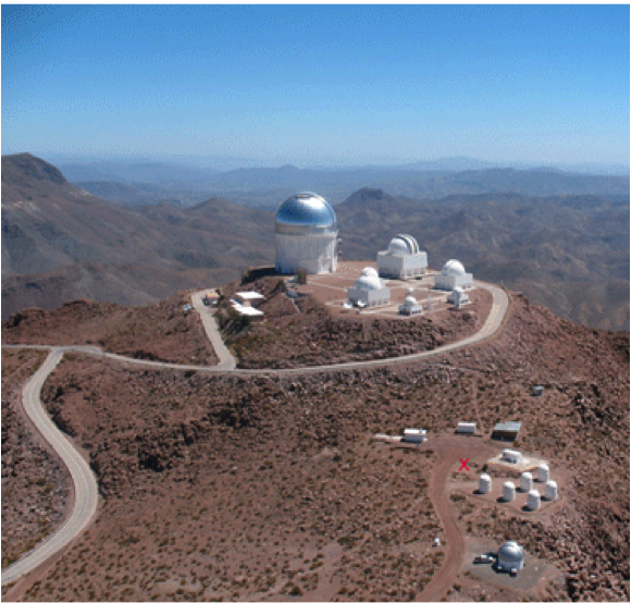 PROMPT is a cluster of small telescope domes situated just down slope from several large telescopes on the top of the mountain. There is blue sky above and distant mountains in the background.  One can also see the a white road surrounding the telescopes on the mountain top and a rougher road leading to PROMPT and other small domes near PROMPT.